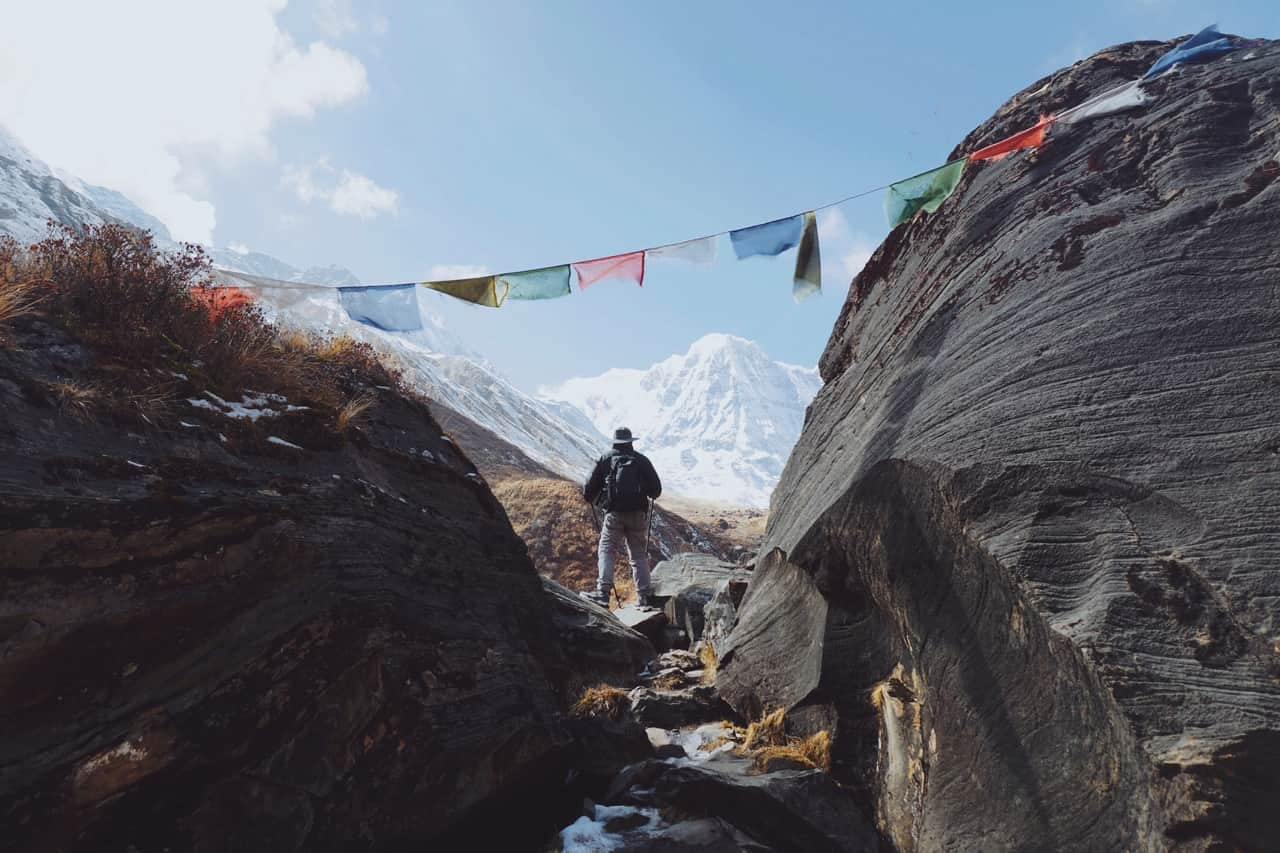 A man views the mountains as the Tibetan prayer flags flutter behind him.