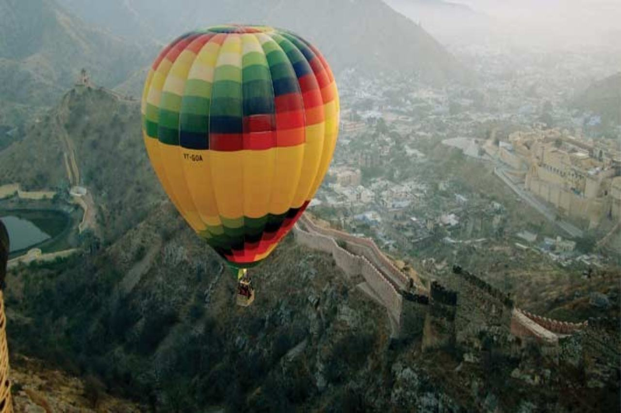 A hot air balloon flies over a hilly fort