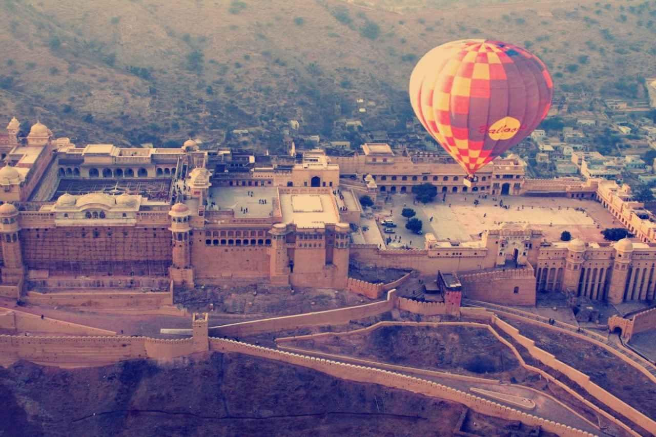 a hot air balloon flies over an ancient fort