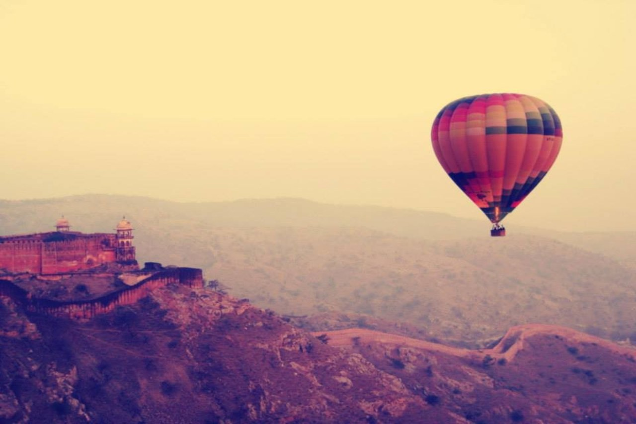 A hot air balloon flies over a hilly fort landscape