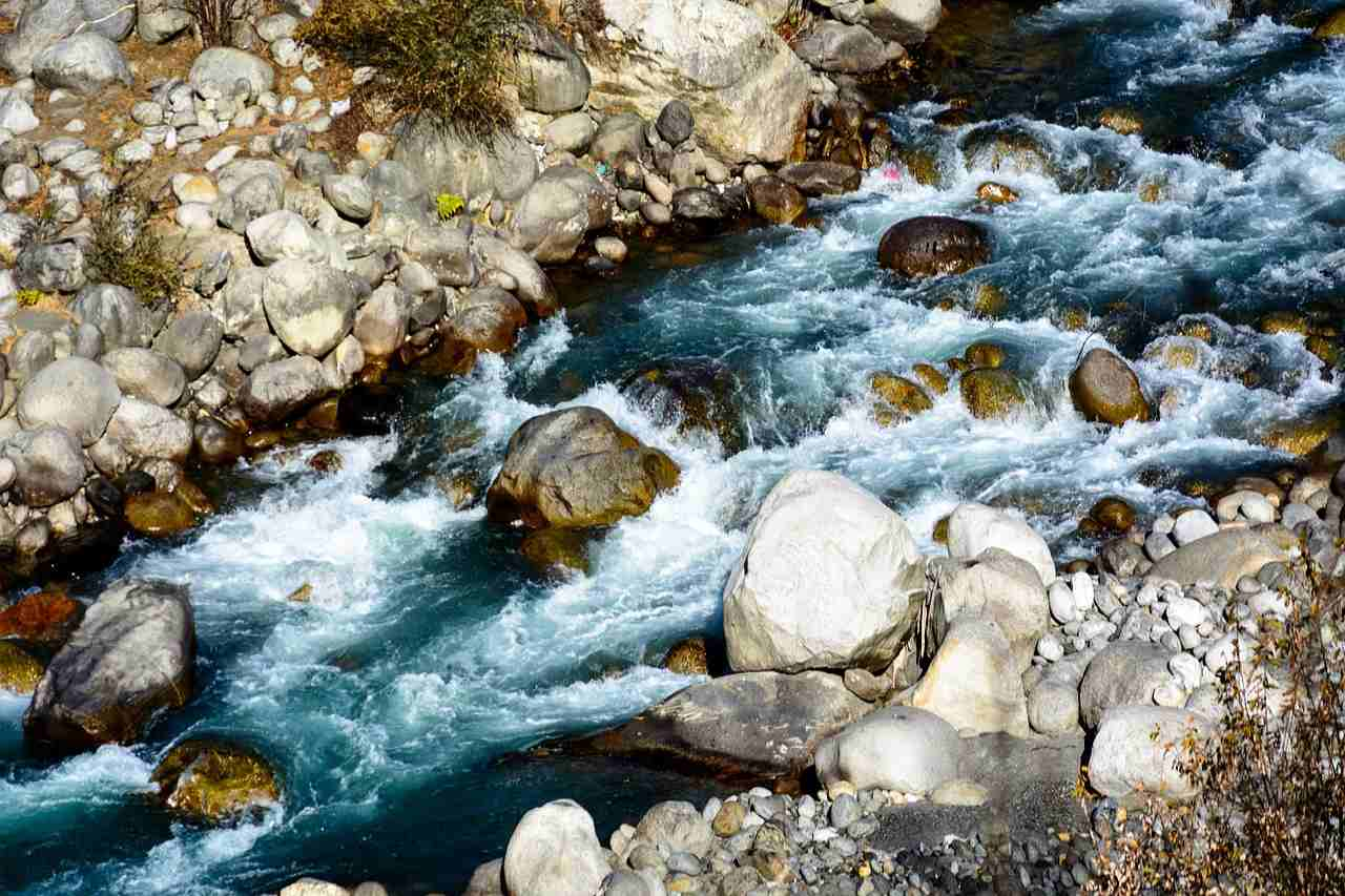 A river gushing over a rocky riverbed surrounded by boulders