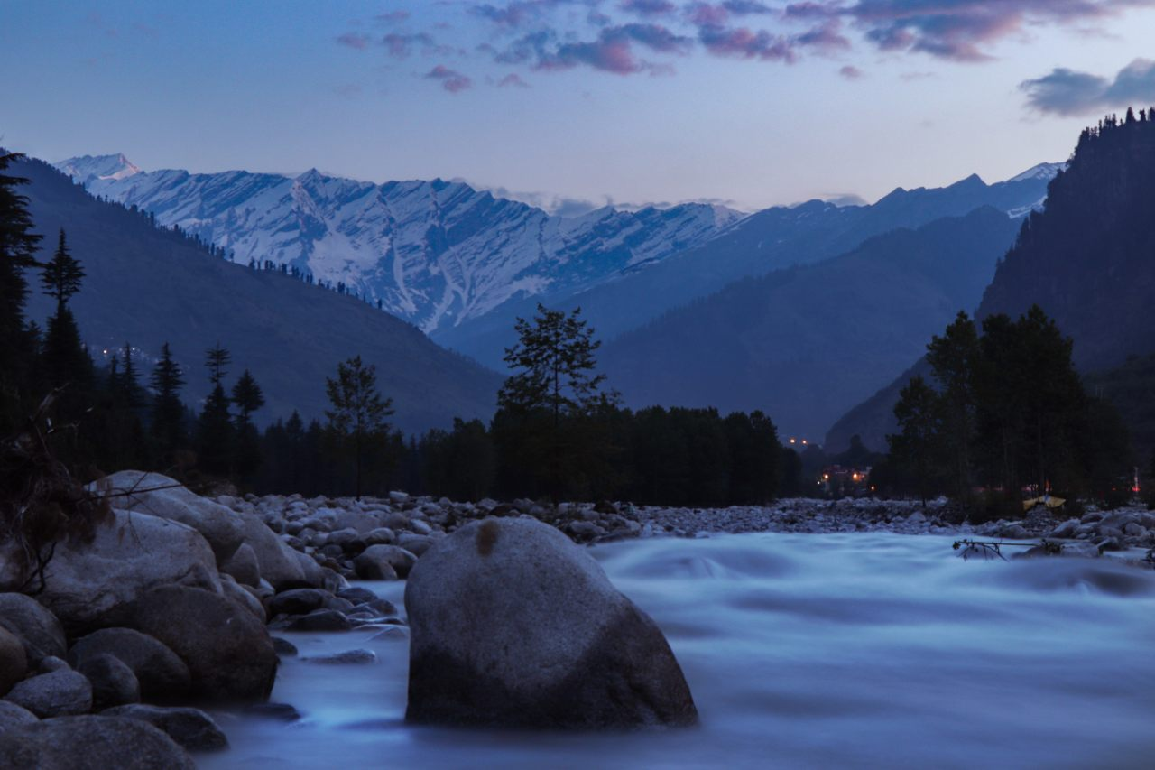 A river flows gently as the mountains stand tall in the backdrop