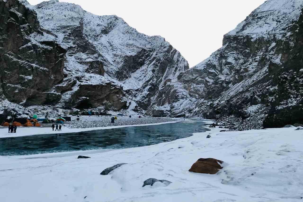 Campsite across a blue river in a gorge