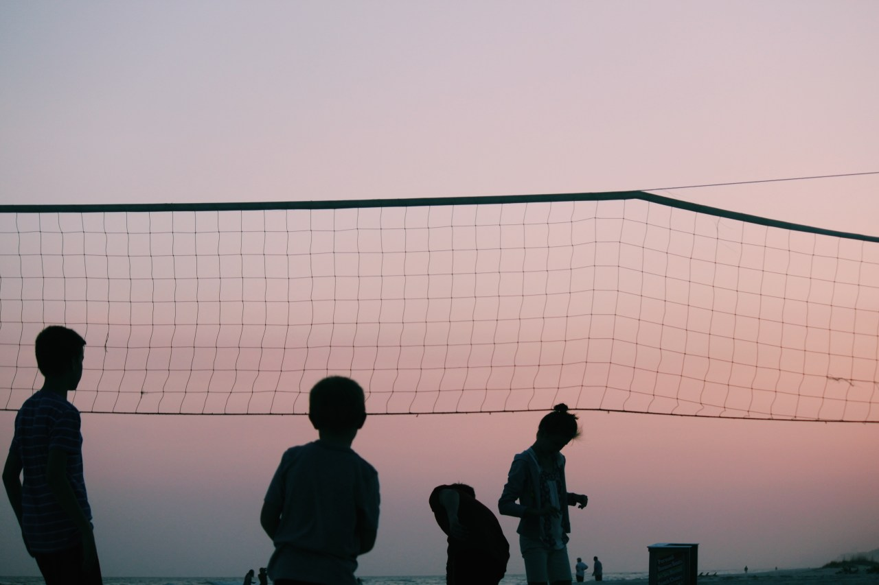 Silhouette of four people playing volleyball during twilight