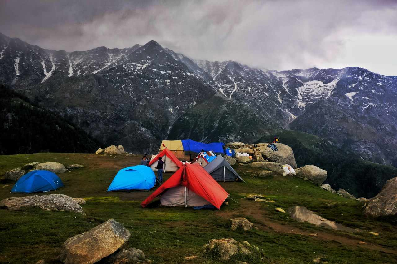 Tents pitched on a rocky ground with towering peaks in the background.