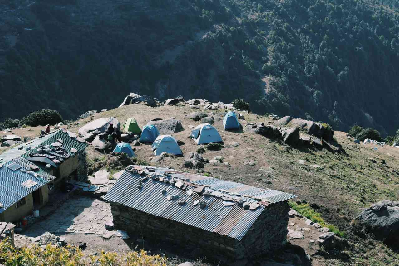 Camps on a cliff looking out at forest covered valley below.