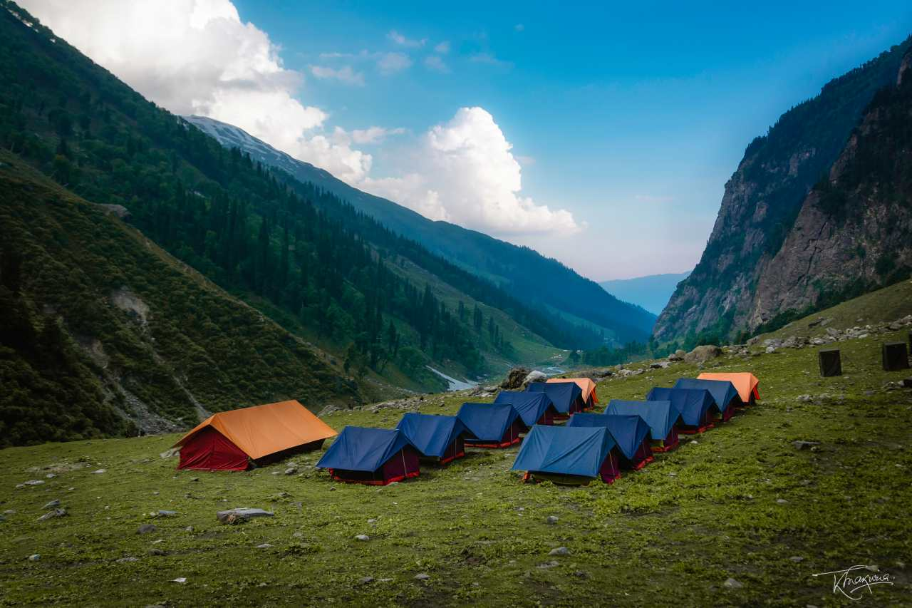 Tents pitched on a green meadow, surrounded by mountains.