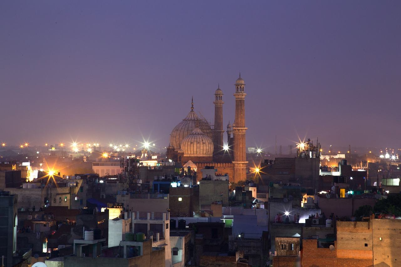 Night photography of a mosque surrounded by buildings.