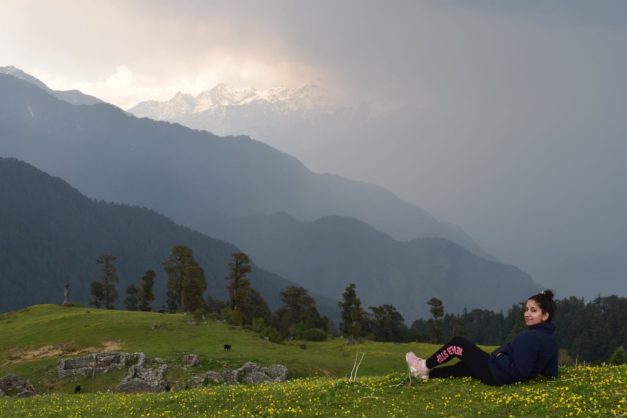 A girl relaxing on a meadow surrounded by mountains as an animal grazes in the distance