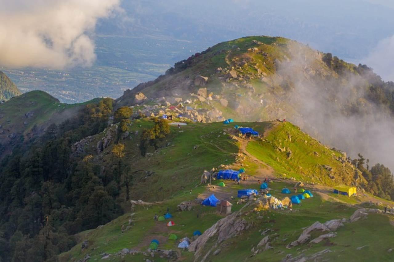 The evening sun illuminates the campsite at a mountain top.