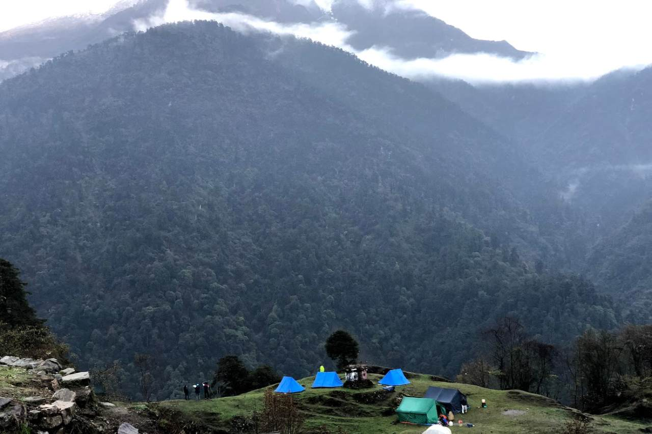 A green carpeted mountain towering over a couple of tents pitched on a cliff.