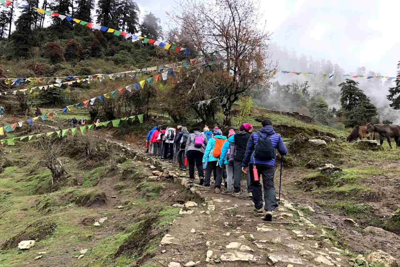 A group of poeple walking in a line on a rocky path.