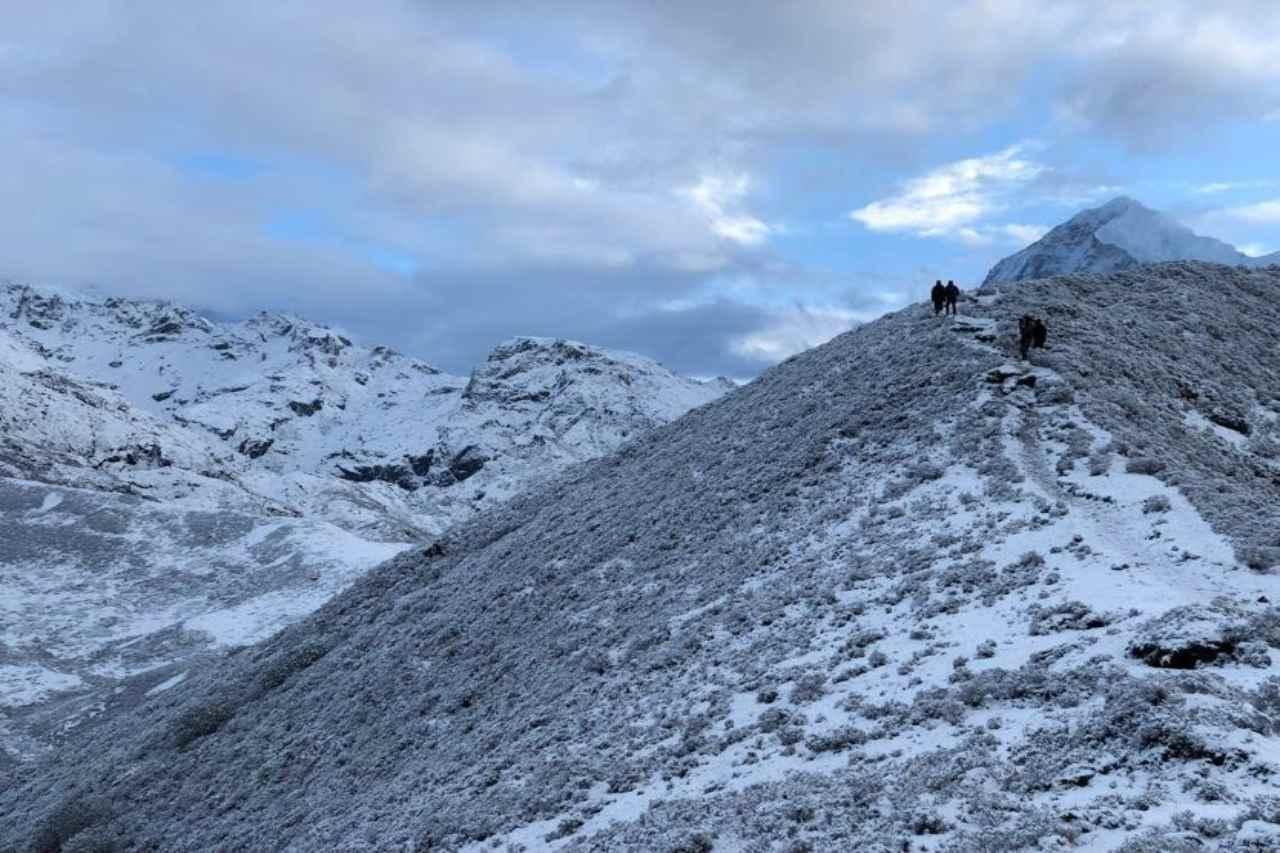 Two trekkers walking on a mountain ridge.