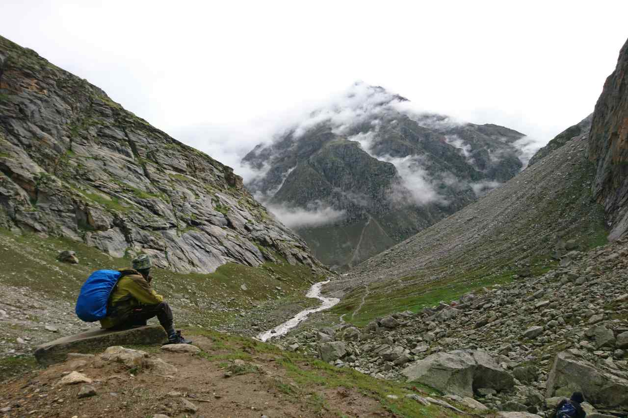 A trekker sits in awe of the sweeping valleys and unending mountains ahead of him