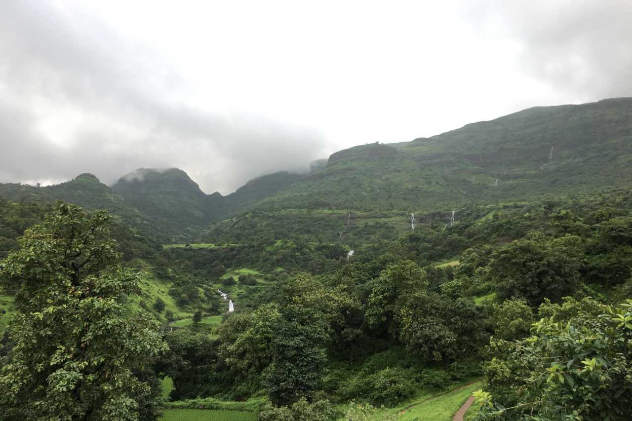 Forest and hills dotted with waterfalls, against a grey sky.