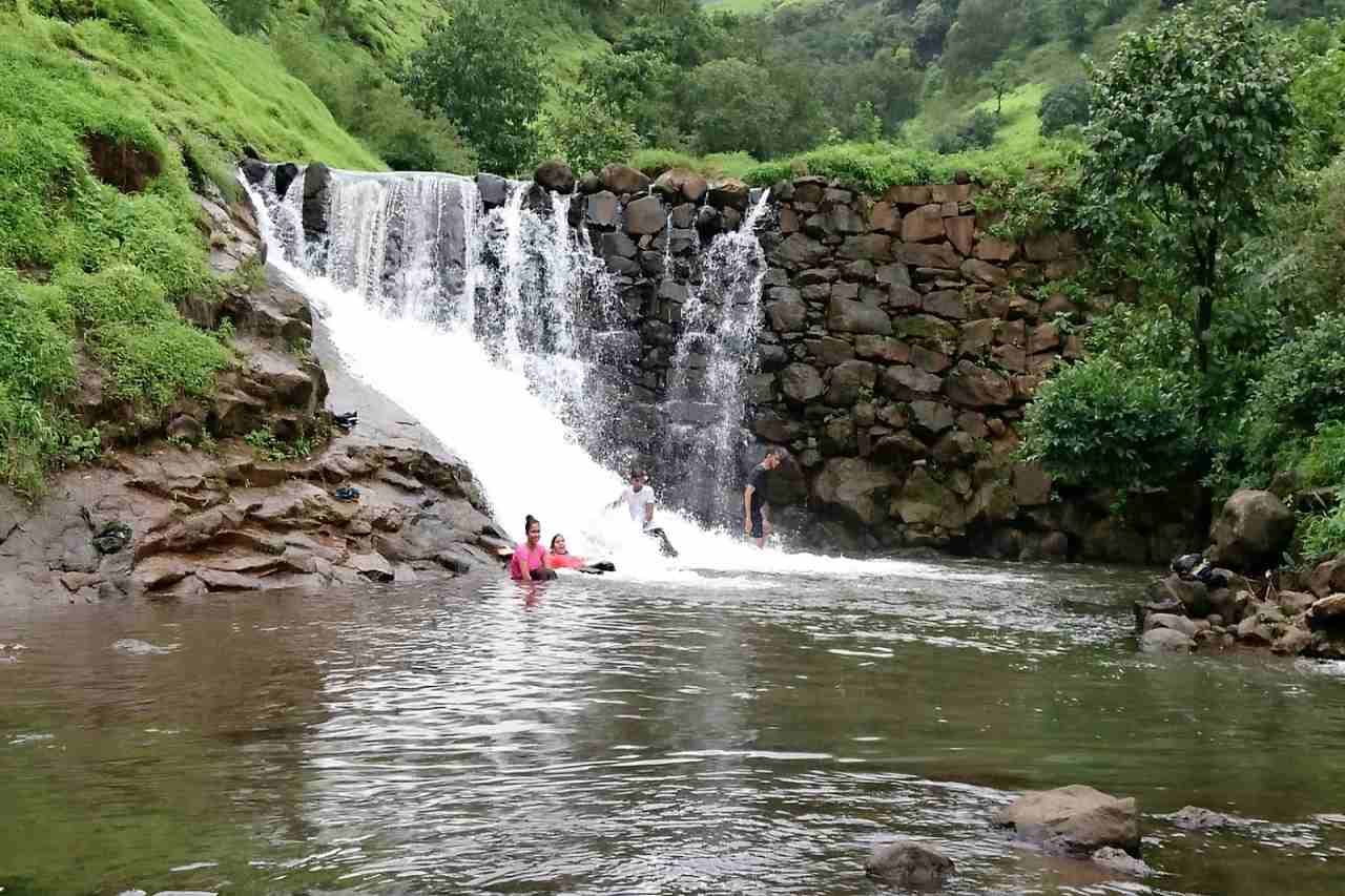 People having fun beneath a waterfall.