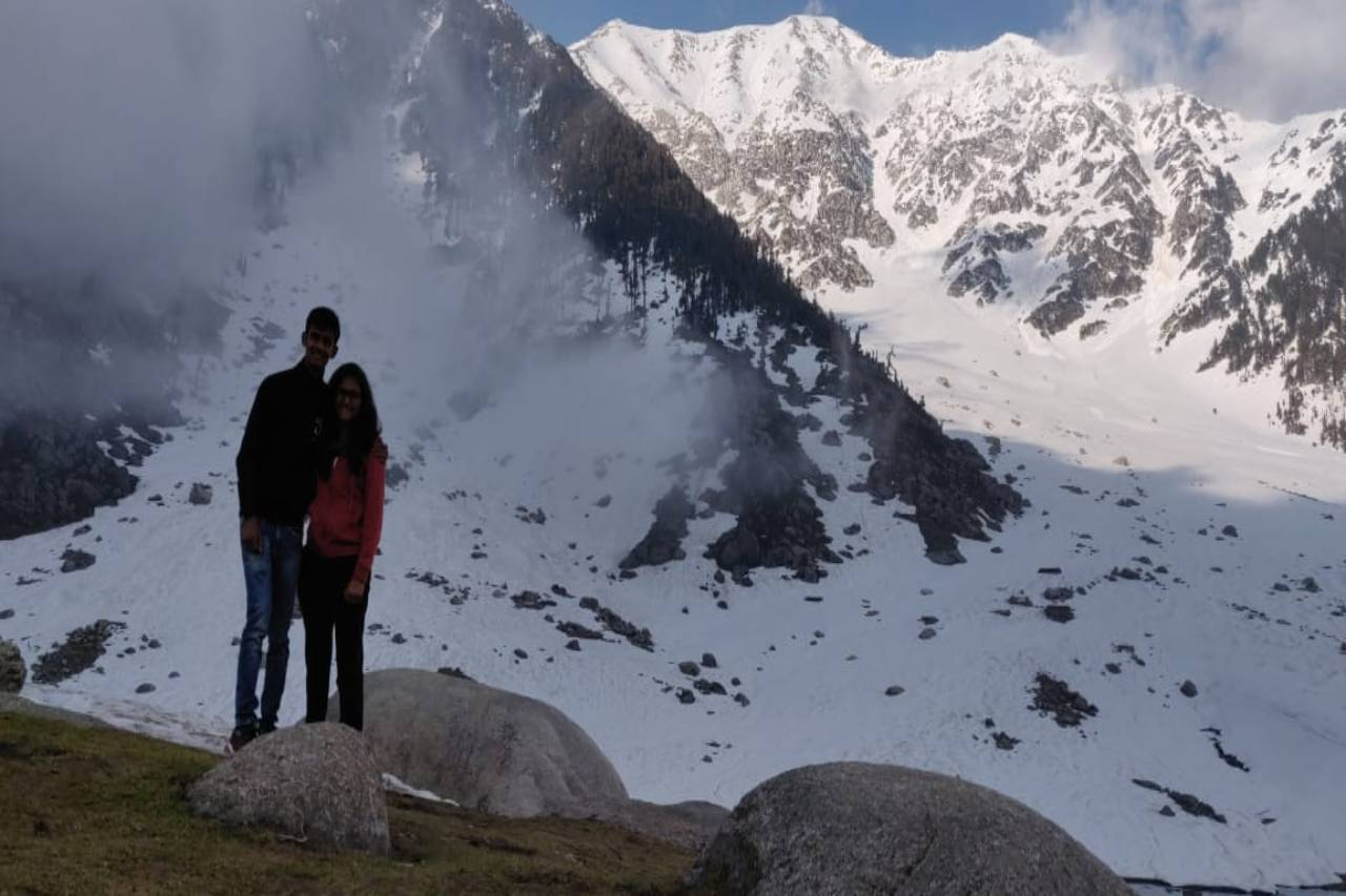 A couple pose in front of a snowy pass