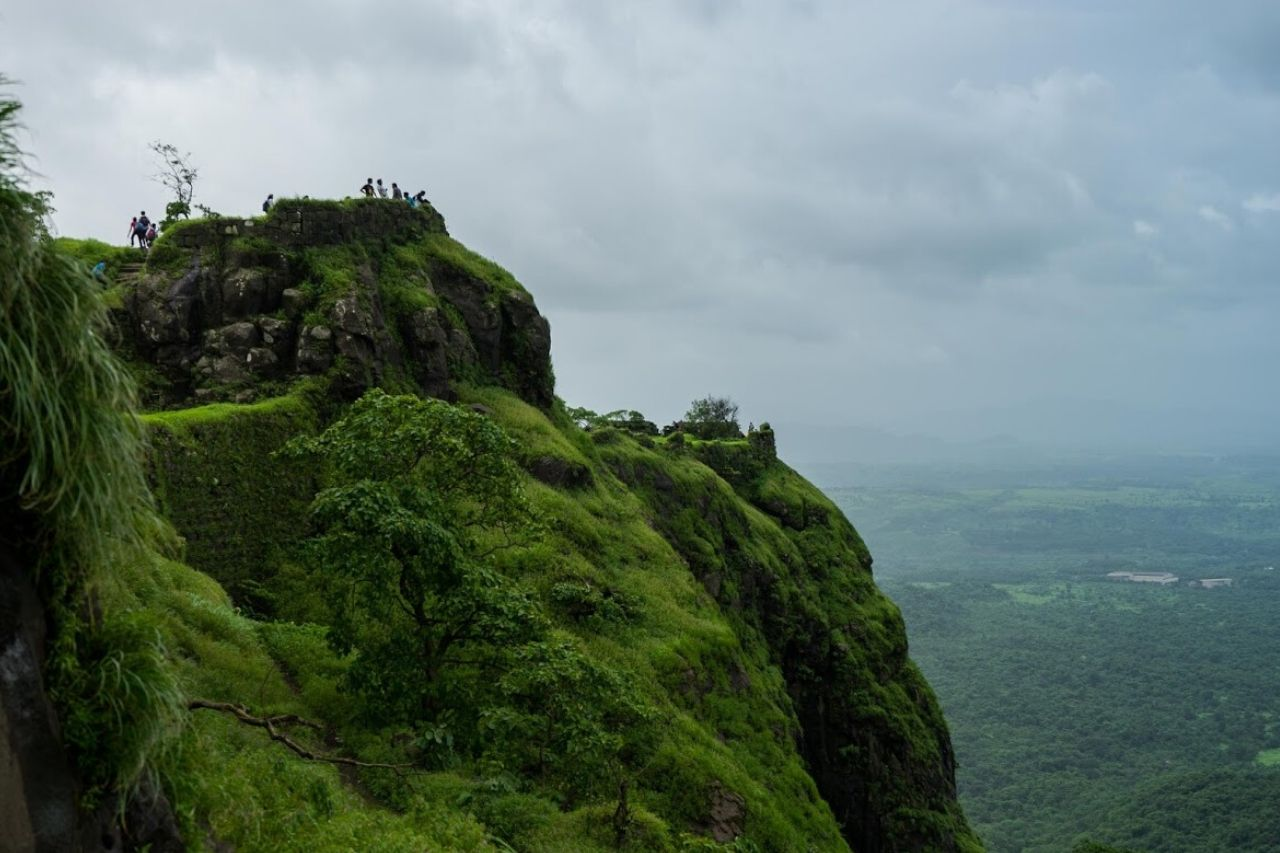 Trekkers stand atop a fort on a rainy day