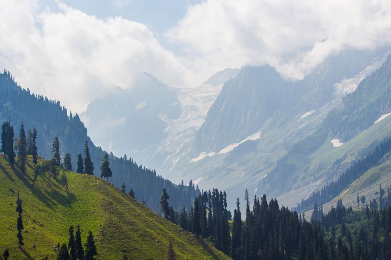 A green valley merges into snow covered valley and snow-clad peaks