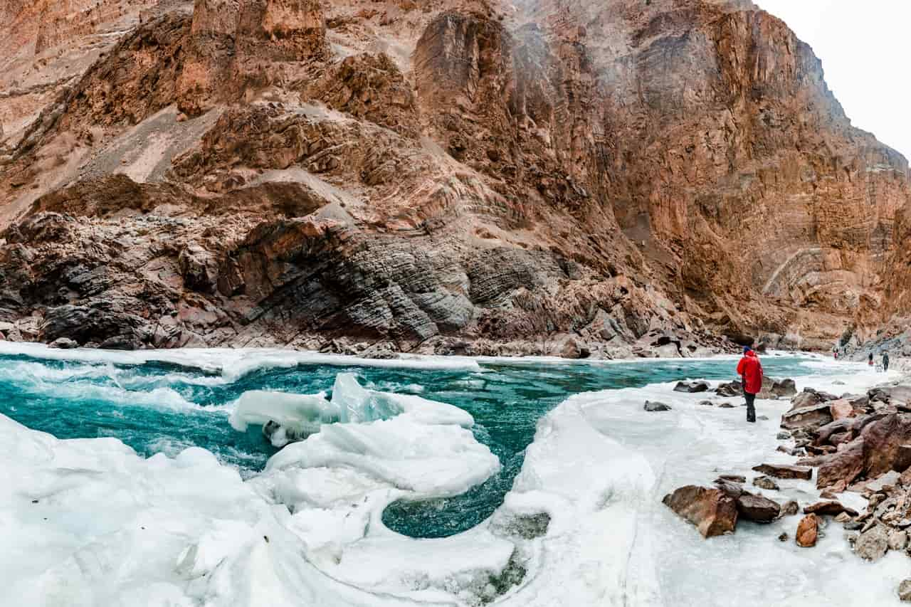 A man stand besides an icy river