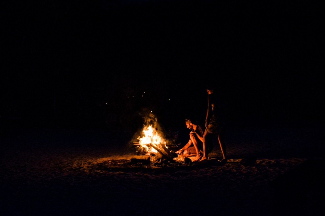 Two people stand near bonfire on a dark night.