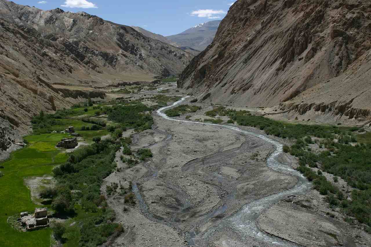 A river meandering through a vast valley through giant mountains