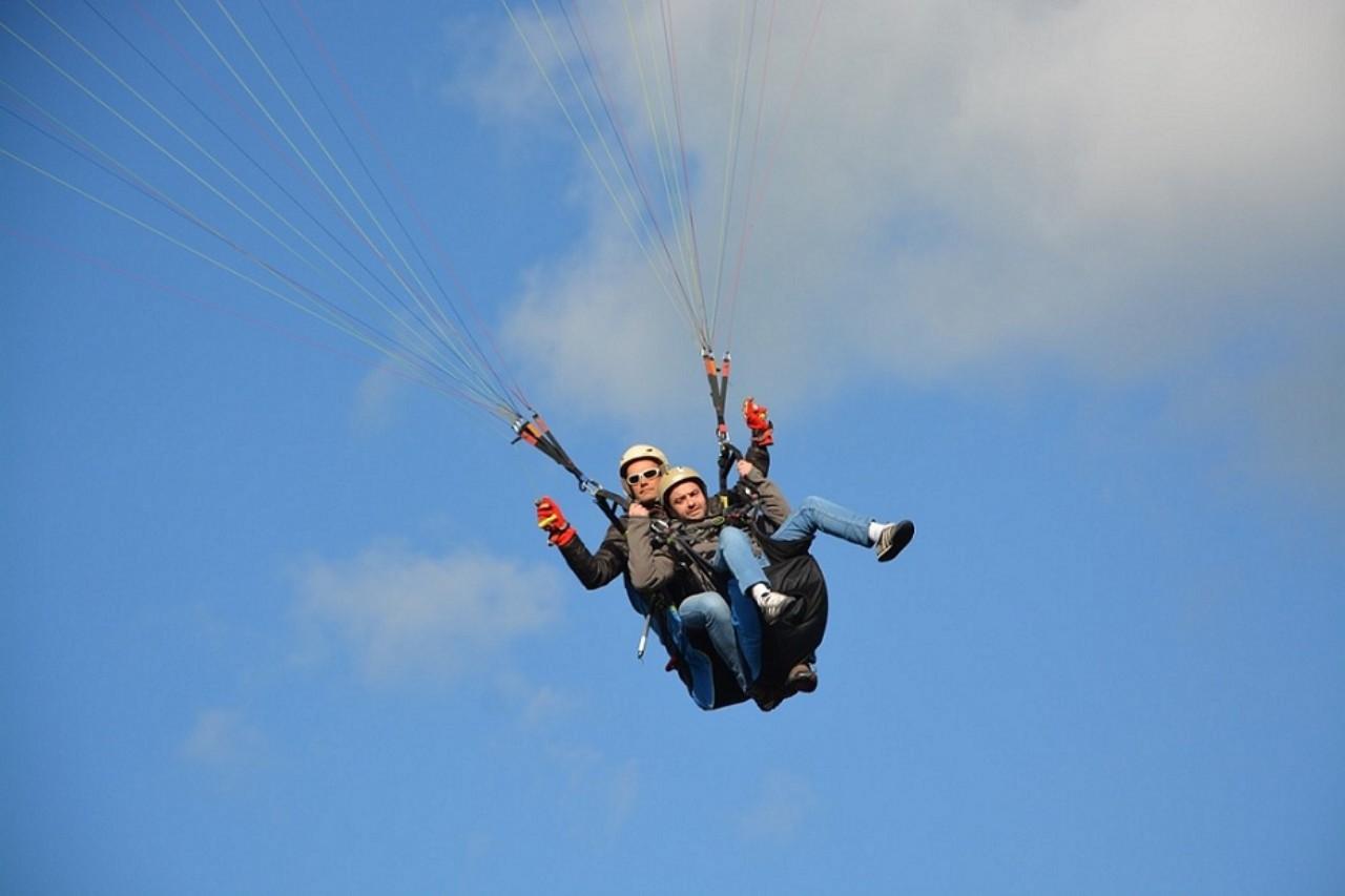 Tandem paragliders mid air.