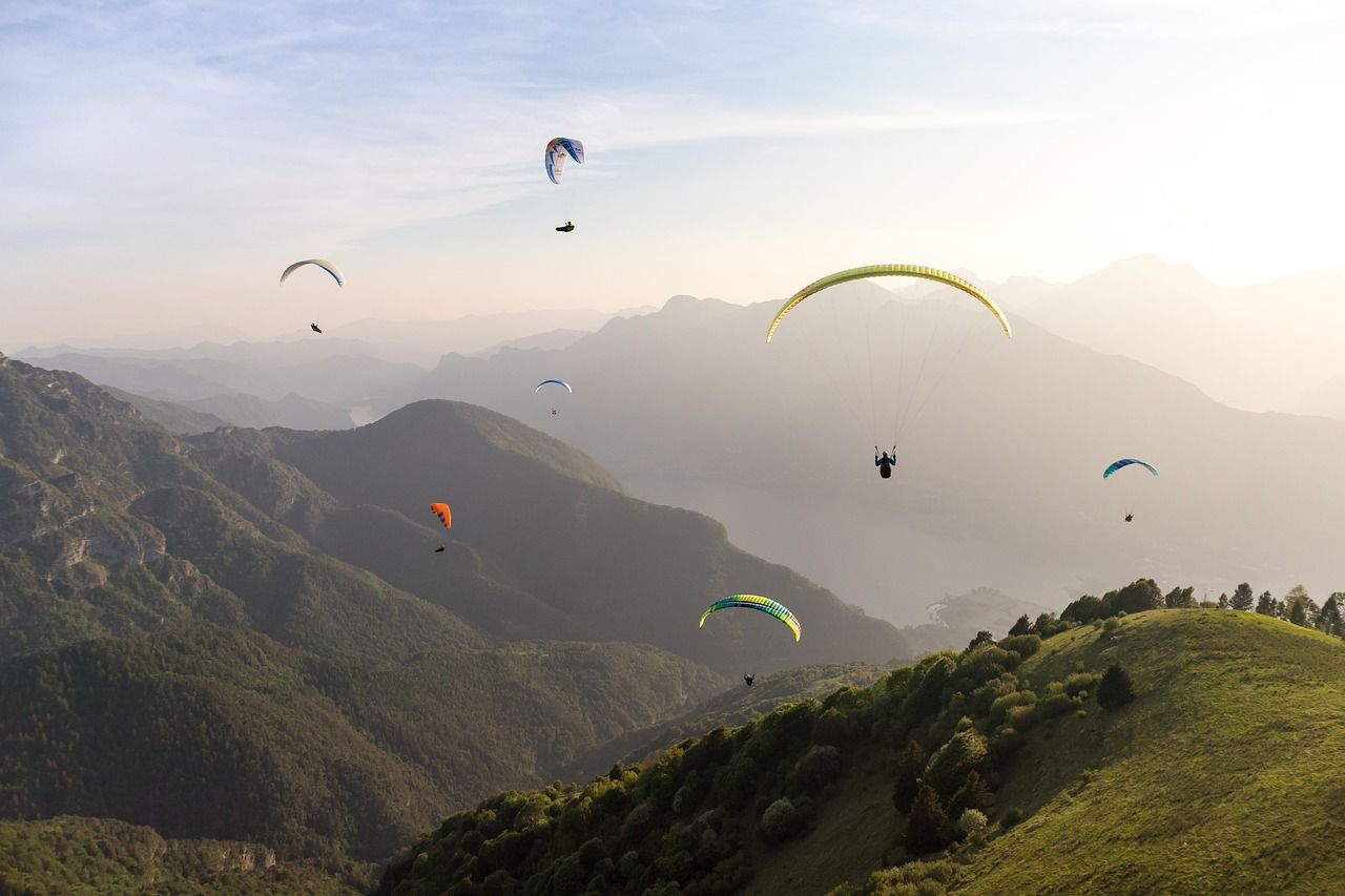 Several paragliders over a hilly green landscape.