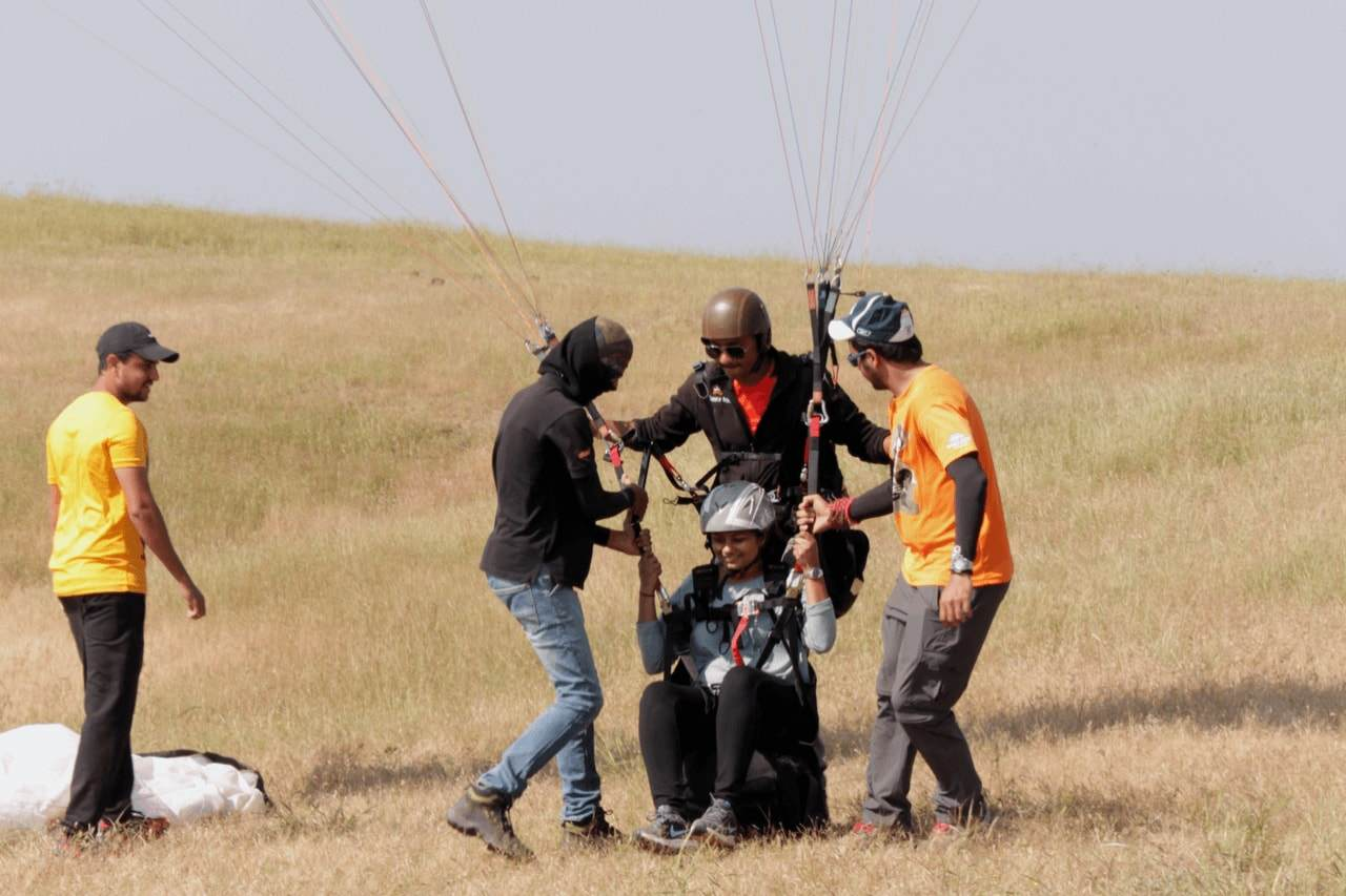 Paragliding crew help a passenger put equipment on.