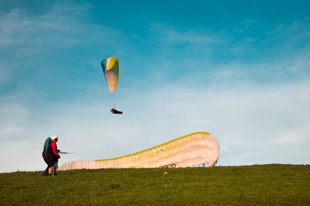 A paraglider watches another about to land.