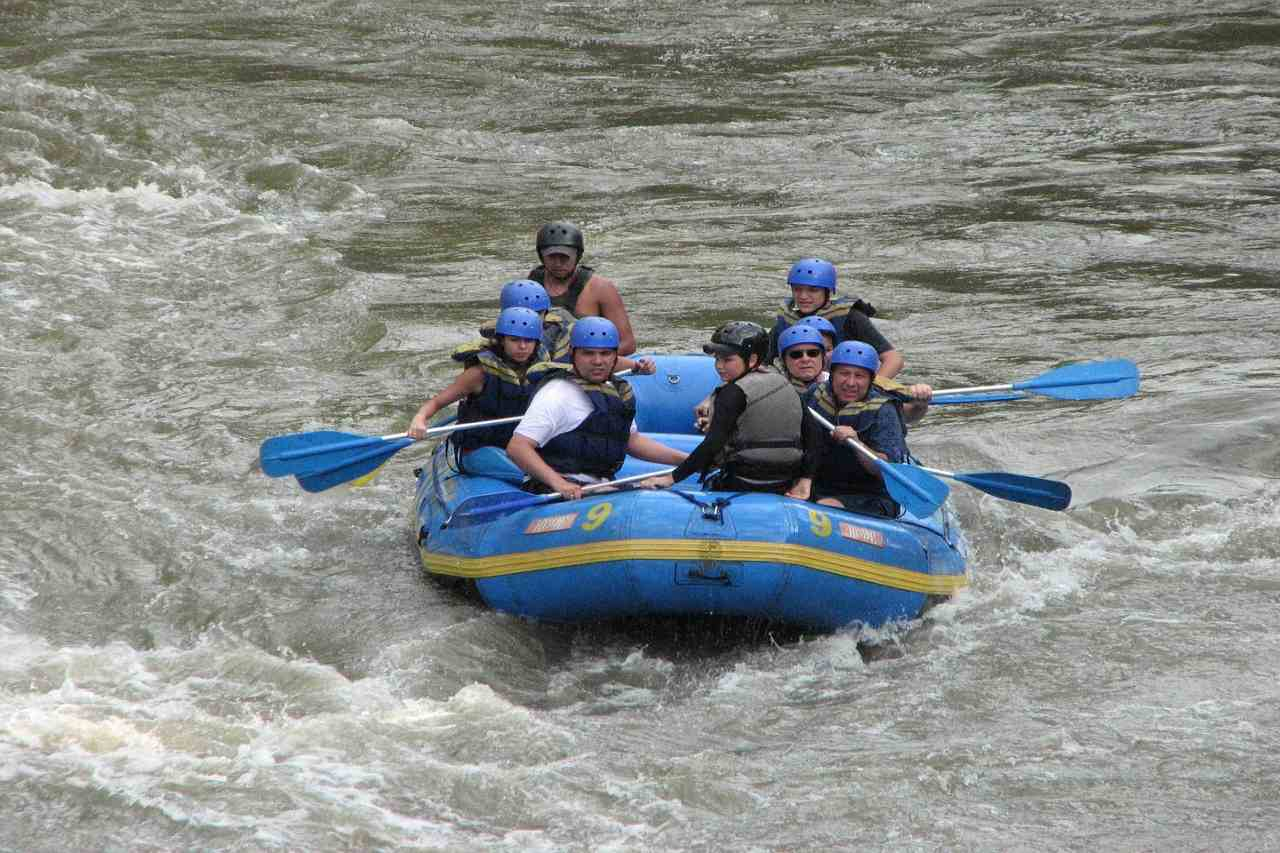 A group of rafter on a blue inflatable boat