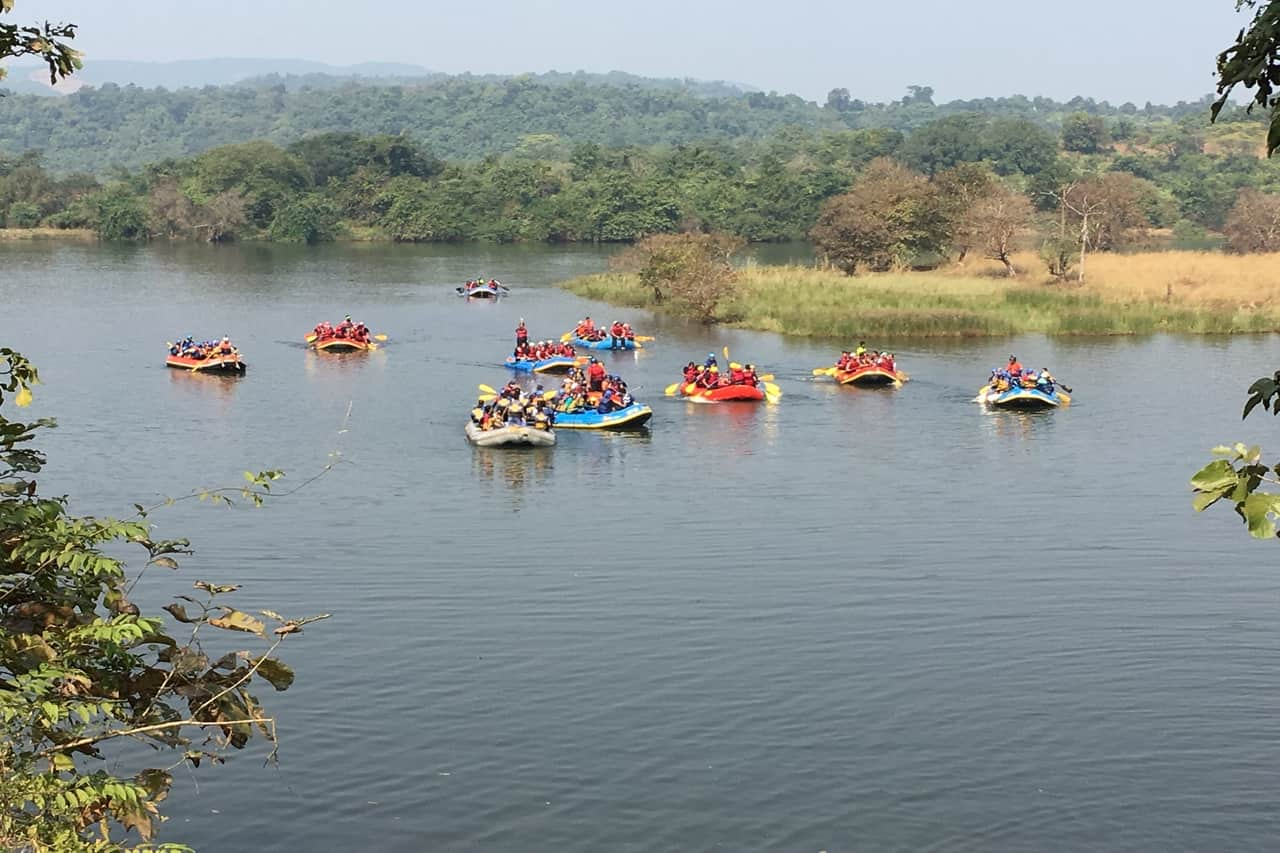 Several rafting boats with rafters navigating a river.