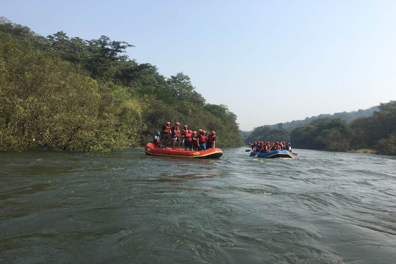 A couple of rafting boats filled with rafters heading out into the river