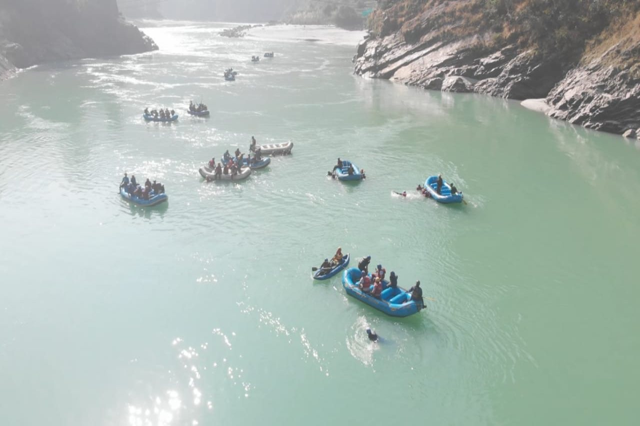 A couple of rafts, with rafters bobbing on a serene blue river