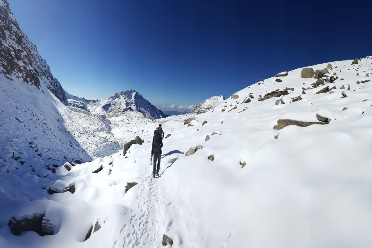 Two people walking on a snowy trail