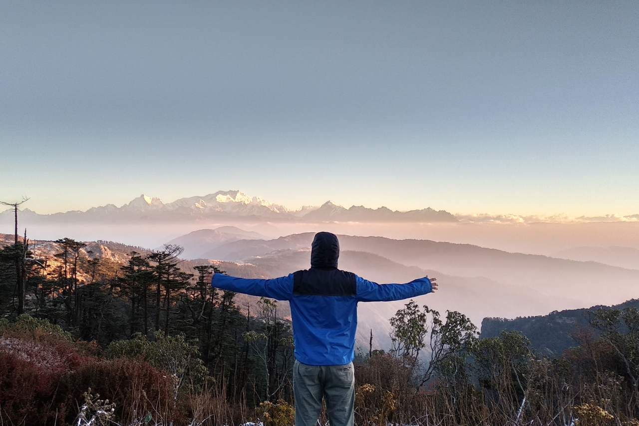 A trekker rejoices the view from a mountain summit of surrounding peaks