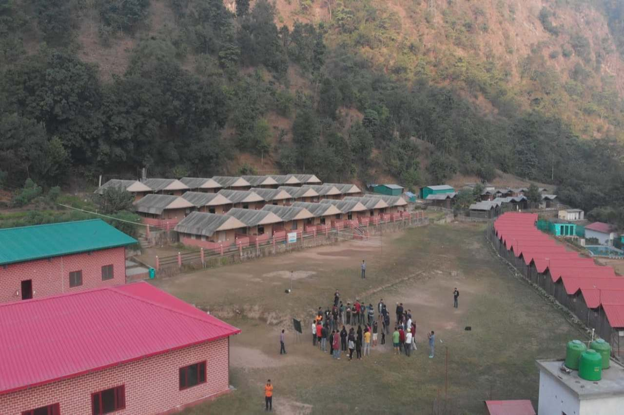 People gathered in the middle of a campsite lined with cottages.