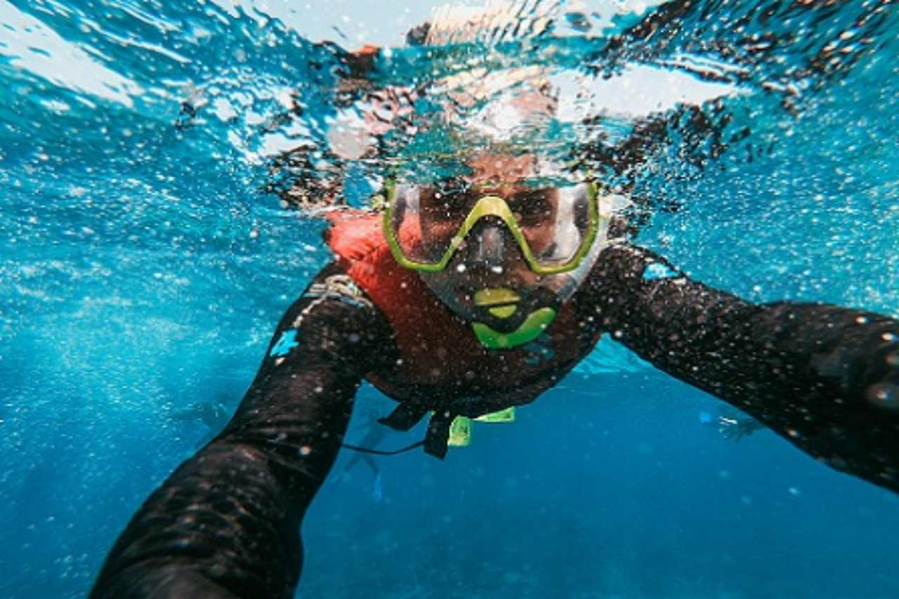 Snorkeller holds camera and takes his own photo underwater.