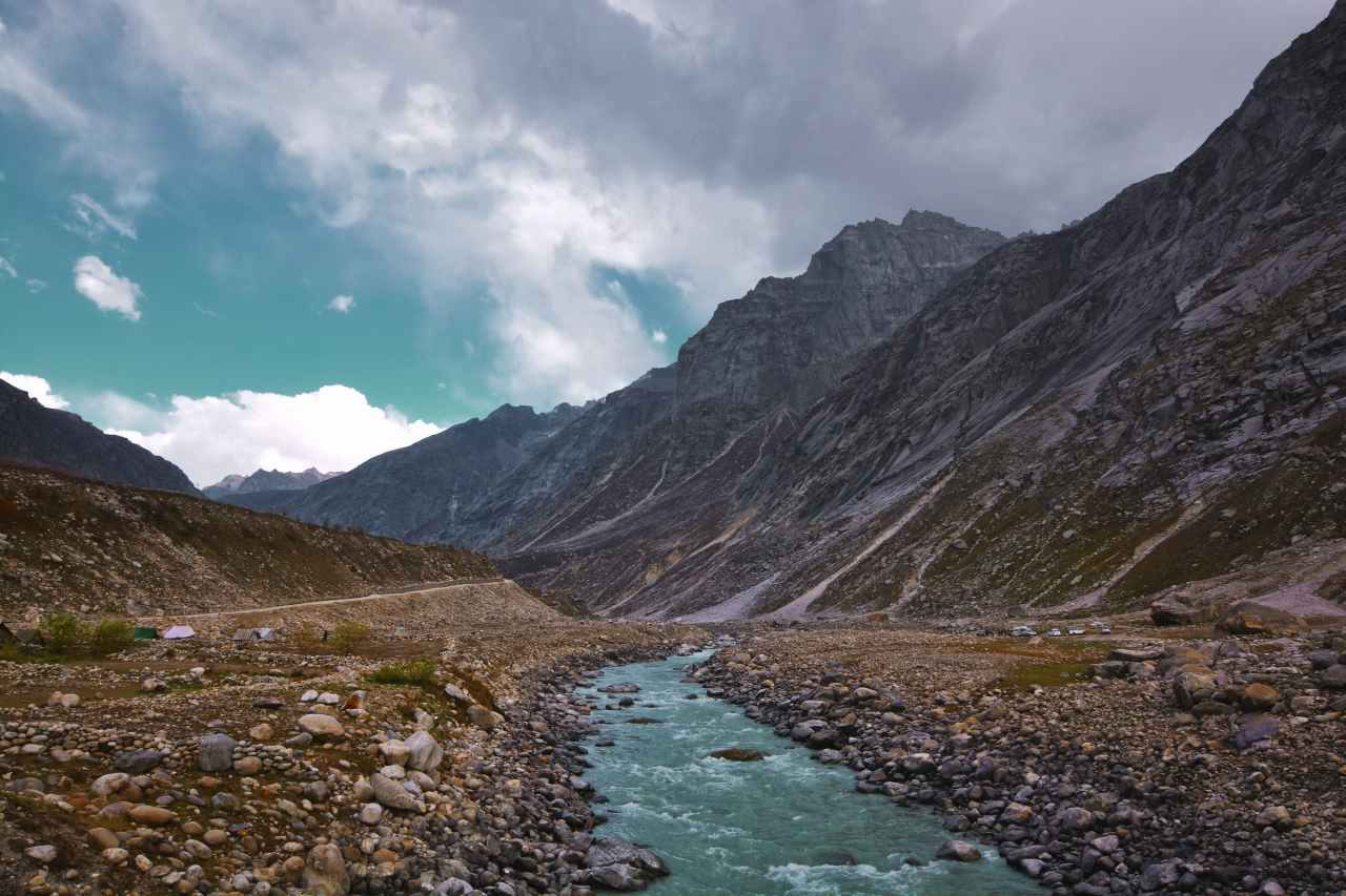 A river flowing across a vast valley surrounded by mountains