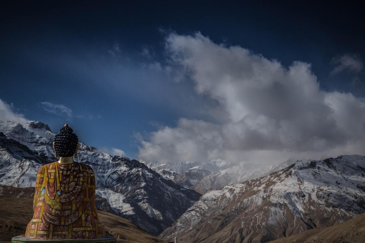 A statue of Buddha overlooking the snowy mountain peaks