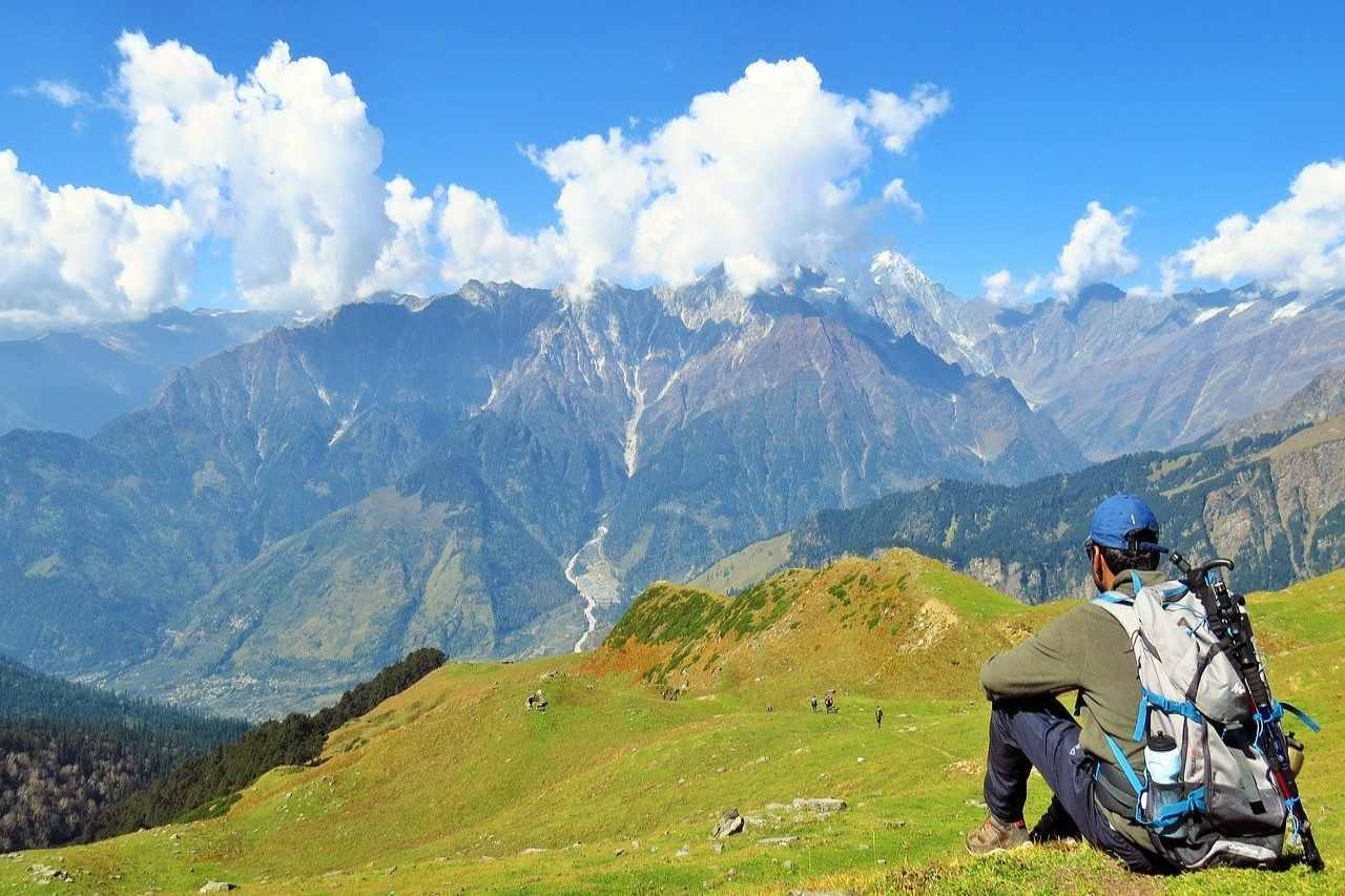 A trekker sits in awe of the unending mountains ahead of him