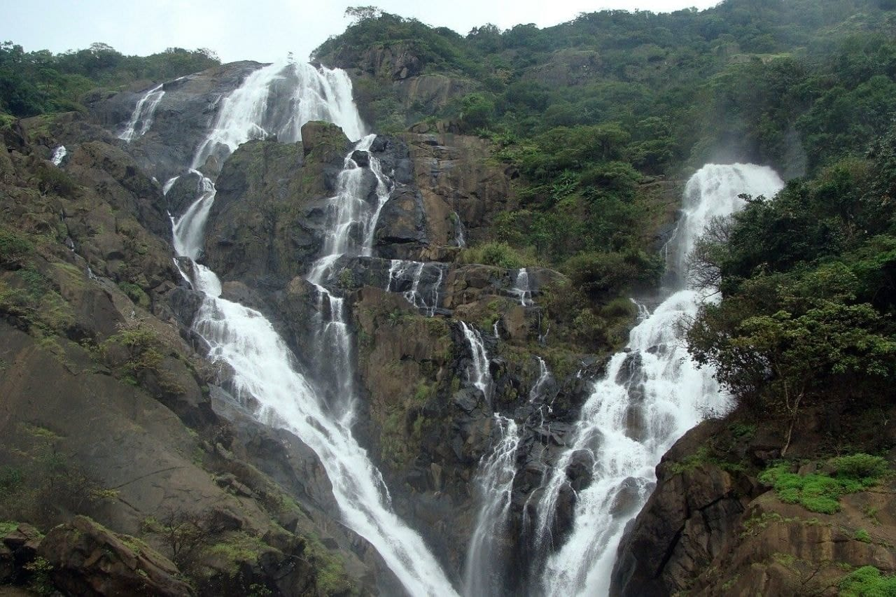 Tiered waterfalls crash down green hill
