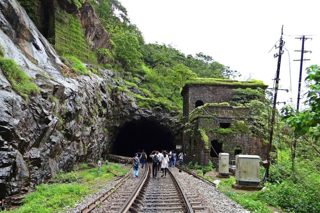 People walk along railway track on rainy day