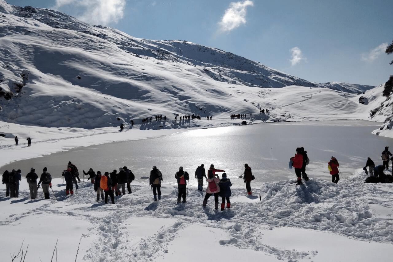 Trekkers gathering around frozen lake on Brahmatal trek.