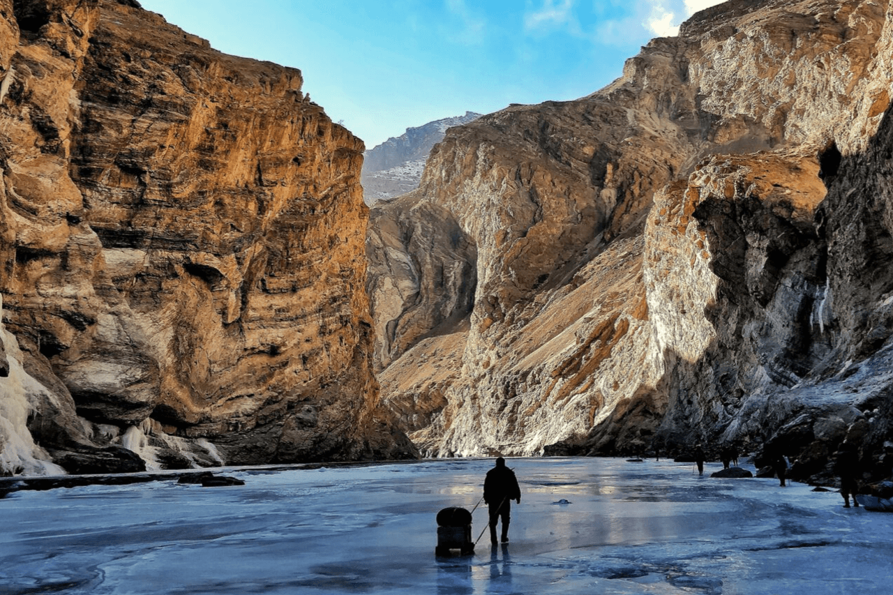 Solo trekker standing beside frozen Zanskar river on Chadar trek