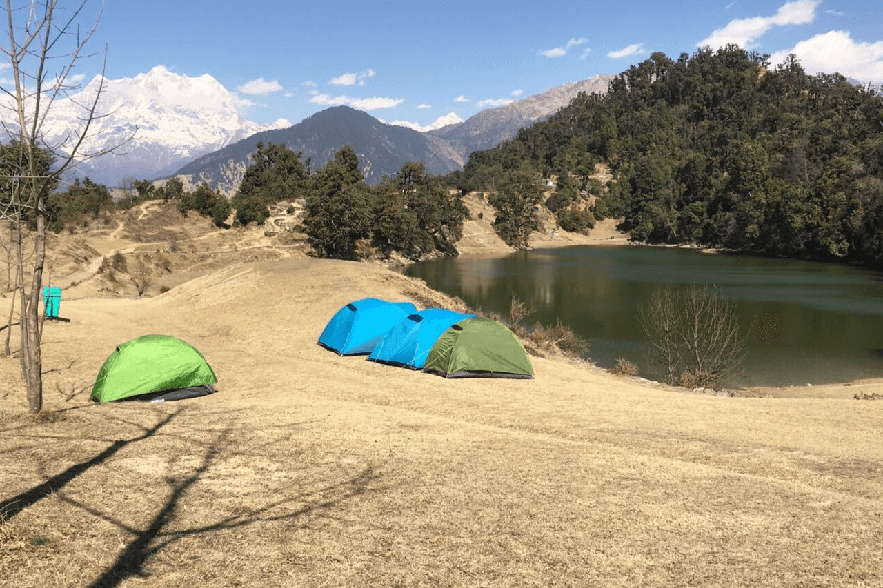 Group of blue and green tents on the banks of Deoriatal lake.