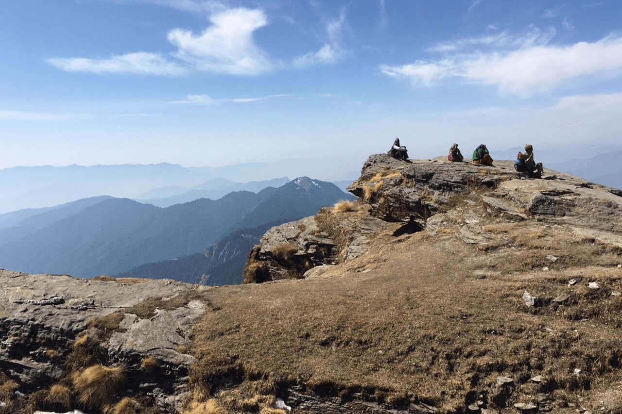Group of trekkers look into the distance from a Himalayan peak.