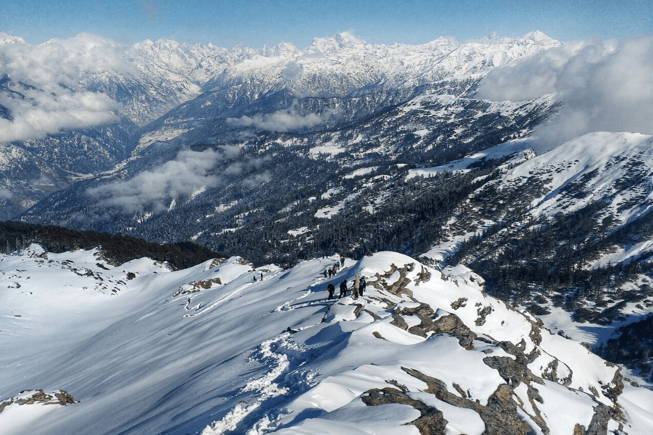 Trekkers converge at the summit of a snowy peak in the Himalayas
