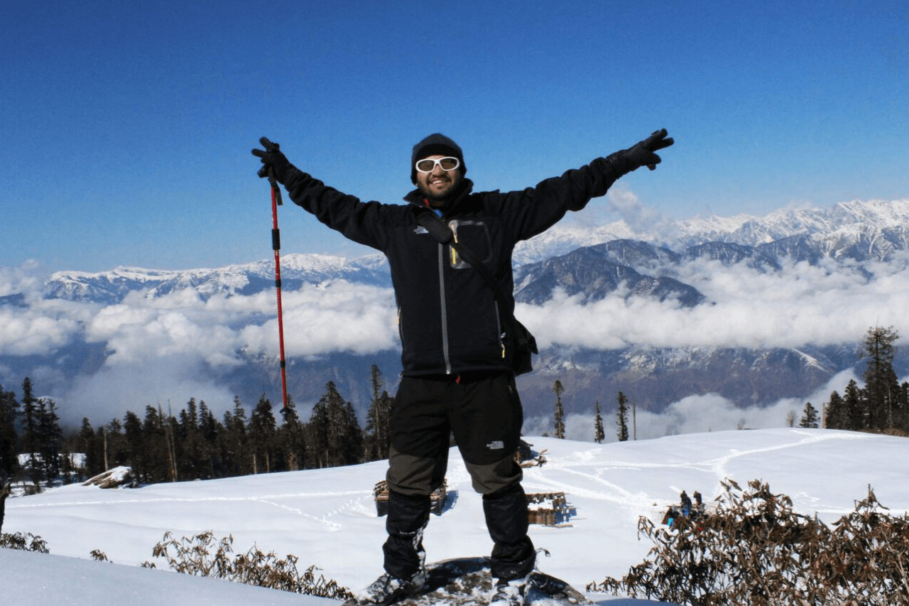 Solo trekker stands with outstretched arms in snowy mountains.