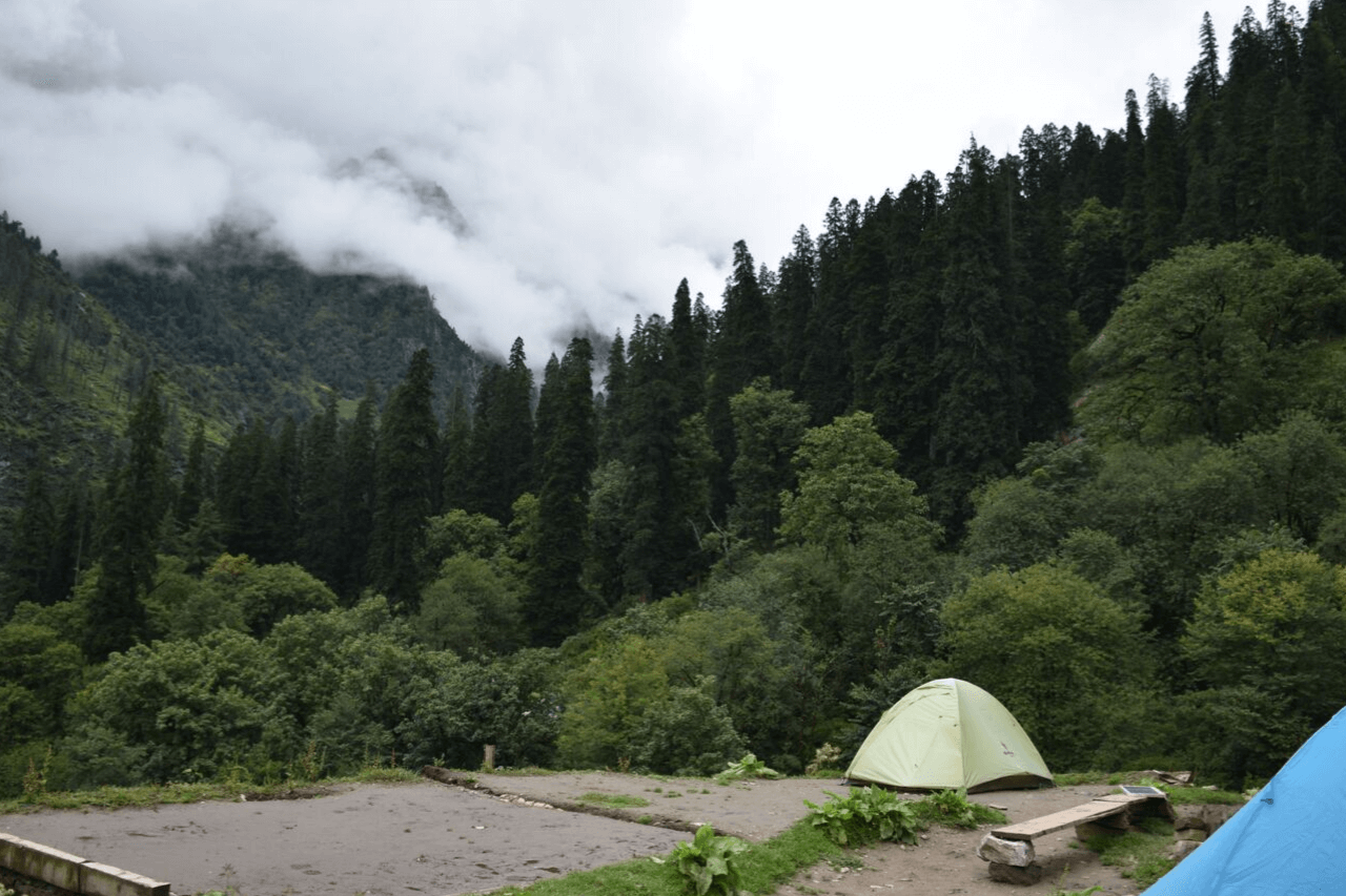 A single tent is perched at a campsite in the mountains.